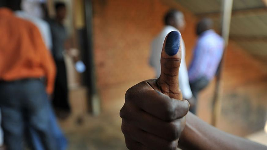 A voter shows his thumbs with ink after voting in 2013 elections. File