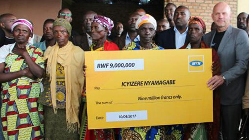 Hofker (right) hands over a dummy cheque to Genocide survivors in Nyamagabe District in April. The telecom firm was penalised in May by the regulator for non-compliance with licenc....