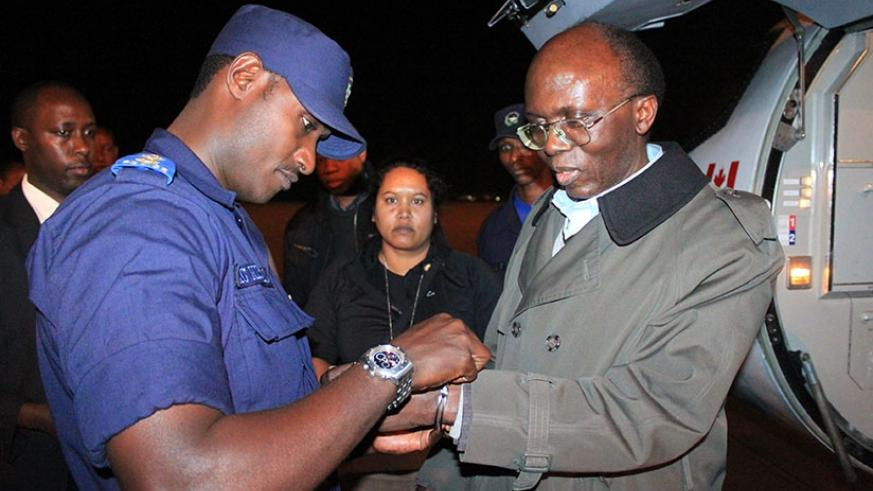 A Rwandan Security police officer handcuffs  Leon Mugesera on his arrival in 2012 at Kigali international Airport from Canada. He was last year sentenced to life in prison over his....