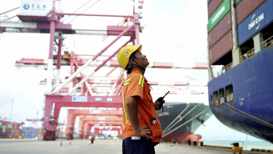 A worker watches as containers are loaded onto a ship in Qingdao in eastern China . Net.