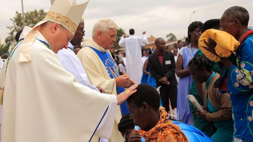 Clerics bless Christians after giving their offerings during the Assumption Day mass at Kibeho on Tuesday. File