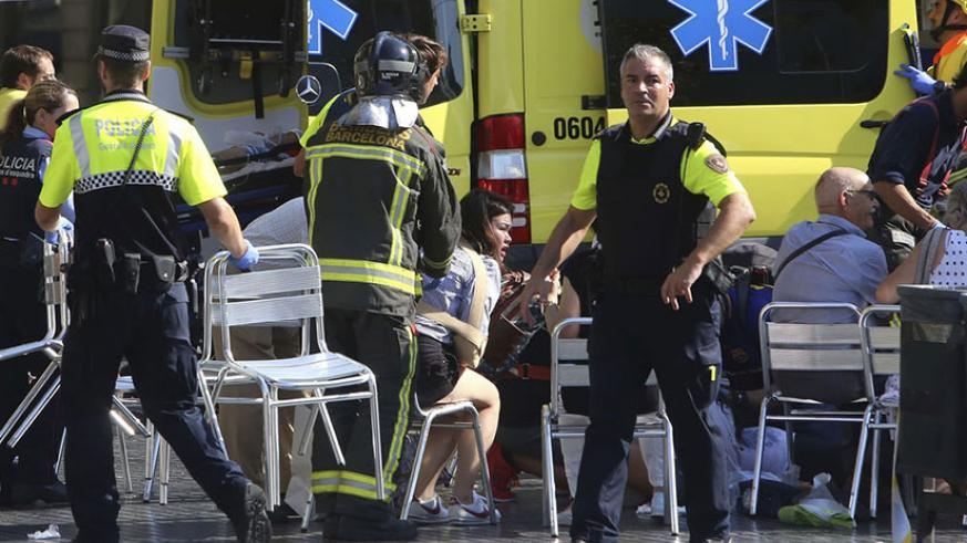 Injured people are treated in Barcelona after a van jumped the sidewalk in the historic Las Ramblas district, crashing into a summer crowd of residents and tourists, police said. /....