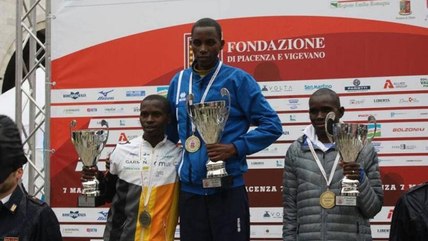 Felicien Muhitira (C) poses on the podium after winning a race in Piacenza, Italy. Courtesy