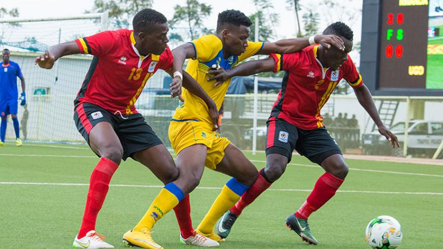 Amavubi striker Abeddy Biramahire fights for the ball with Cranes defenders during yesterday's 2-0 win over Uganda. Although Rwanda won the tie, they lost 3-2 on aggregate. / Timot....