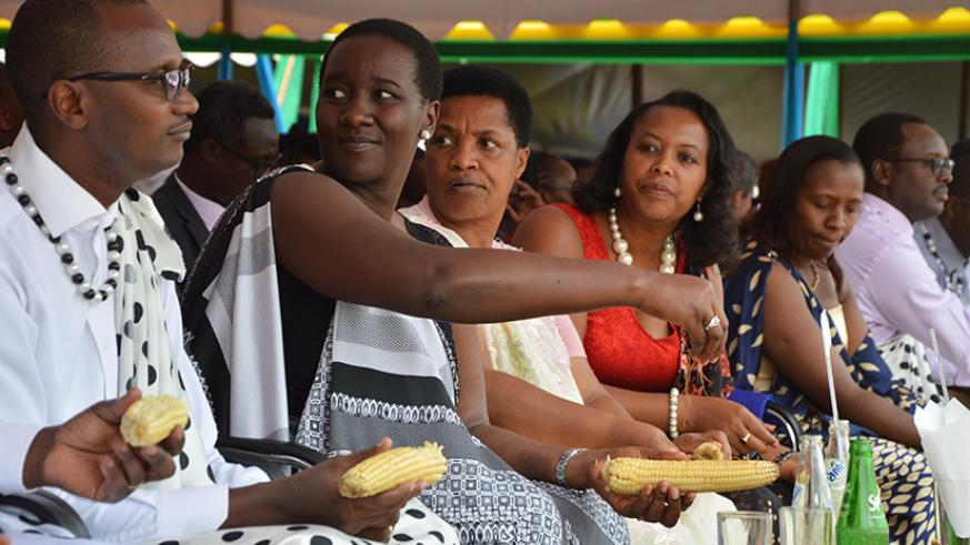 Officials, including Sports and Culture minister Julienne Uwacu (2ndL) and Gender and Family Promotion minister Esperance Nyirasafari (2ndR), eat boiled maize as part of Umuganura ....