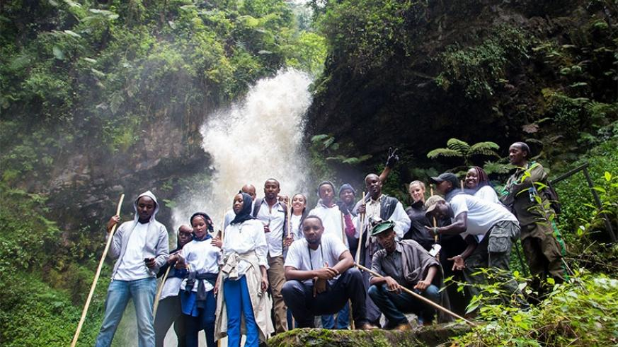 Local and foreign tourists pose for a photo at the Kamiranzovu waterfalls in Nyungwe National Park. the firm will also market Rwanda as a tourist destination under the deal. File.