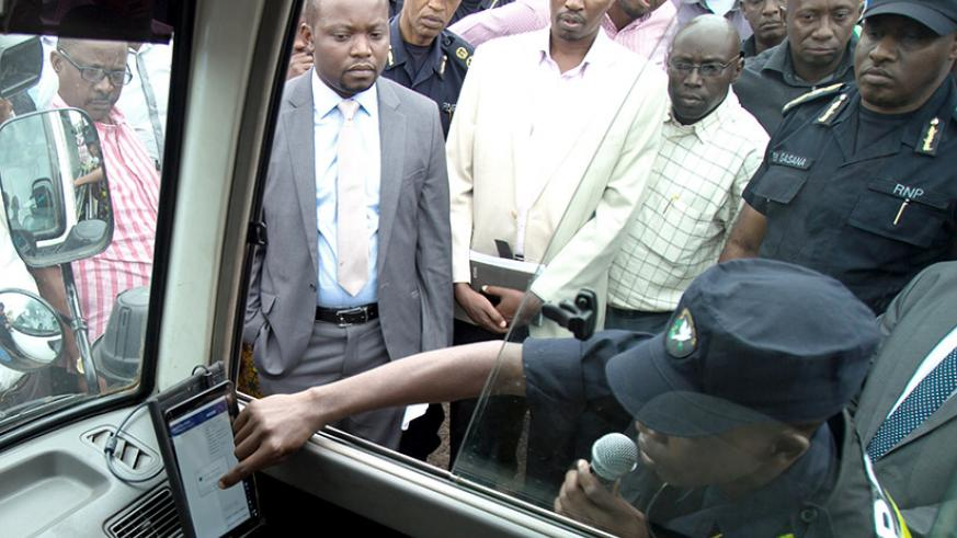 A traffic officer shows government officials how speed governors work in public vehicles. / File