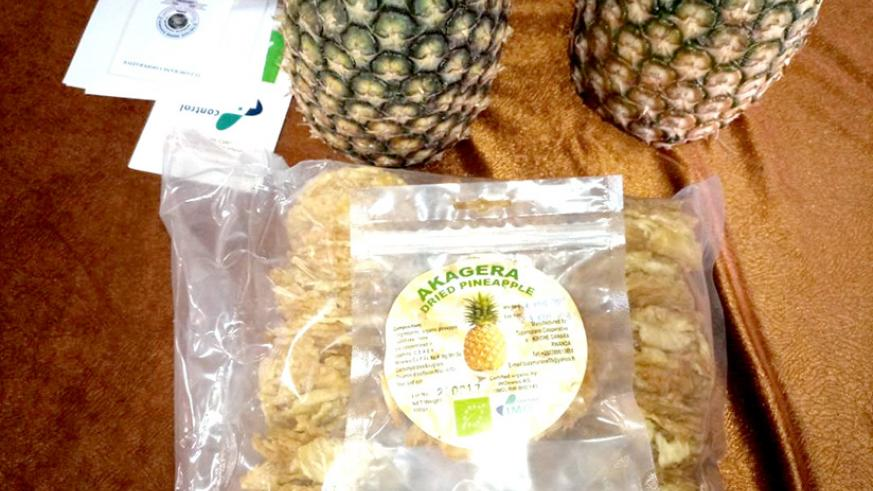 Sample of packaged dried pineapple apple which Tuzamurane Cooperative exports to France. In the background, there are two fresh raw pineapples. / Emmanuel Ntirenganya