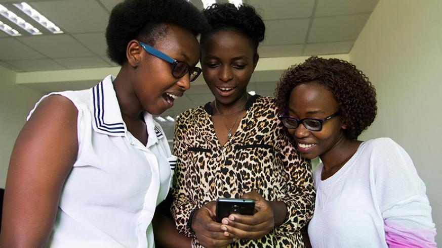 Tantine founder Sylvie Uhirwa (middle) together with Consolatrice Byiringiro, and Marie-Claire Umuhoza look on as more users download the app. / Faustin Niyigena