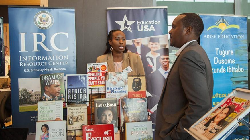 Thais Ruboneka, the information resource centre director at the US Embassy in Kigali talks to a visitor during the book exhibition as part of International Literacy Day yesterday. ....