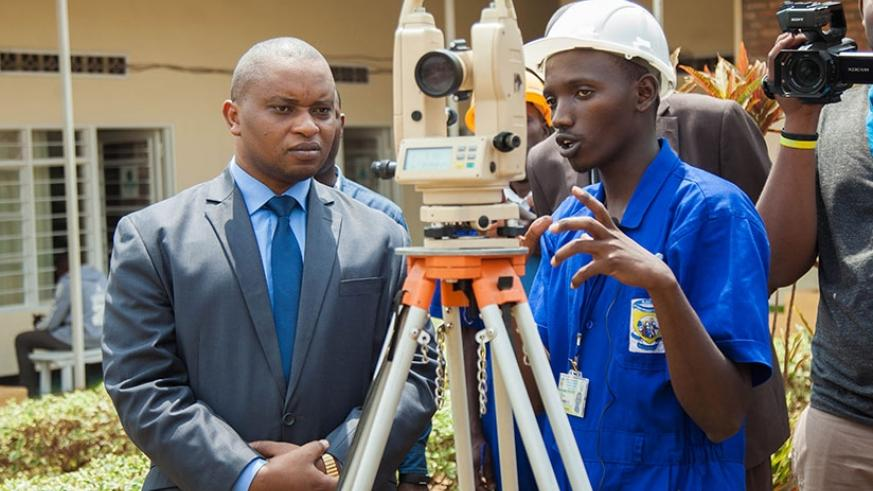 A student from Saint Joseph Integrated Polytechnic explains to Minister Rwamukwaya how to use total station during a practical exam yesterday. (Nadege Imbabazi)