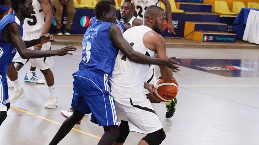 Patriots' Kami Kabenga (with ball) is blocked by a Hawusa players during the first half at Lugogo Indoor Arena on Sunday. Patriots won the game 110-43. Courtesy.