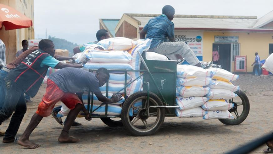 Members of a traders' cooperative of people living with disabilities push a cart of goods from Gisenyi town to cross into Goma in DR Congo last week. Faustin Niyigena.