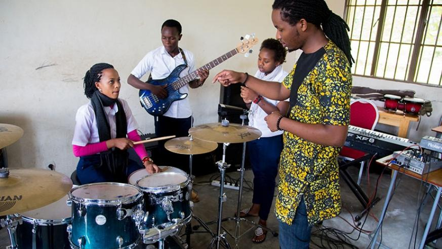 Alumni Igor Mabano instructs singer Ruth Kanoheri Christmas on how to drum. She is in level four at the Rubavu-based Nyundo School of Art and Music. The director of its three-year-....