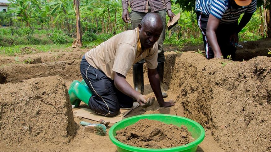 Ntagwabira and one of the two professional Rwandan archaeologists scrub soil from the former king's palace for sample analysis. (All photos by Faustin Niyigena)