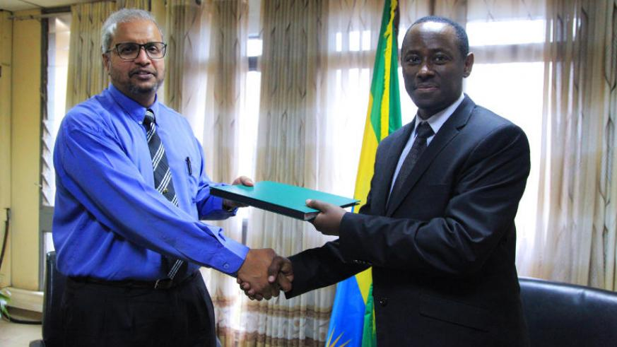Prof Sid Nair exchanges documents with Dr Emmanuel Muvunyi after signing the MoU in Kigali yesterday. / Sam Ngendahimana