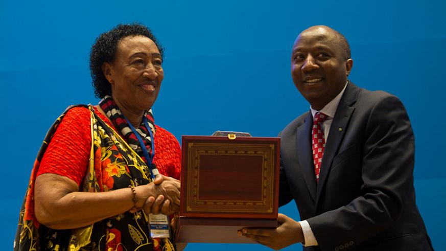 Premier Dr Ngirente (R) awards Francoise Nyirantagorama of Ecole La colombiere an award during the Taxpayer's Day in Kigali yesterday. Timothy Kisambira.