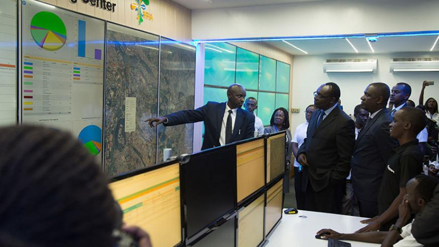 Robert Mugabe, the coordinator of the cargo tracking system, explains how the system works to former trade minister Francois Kanimba (C), and other government officials during laun....