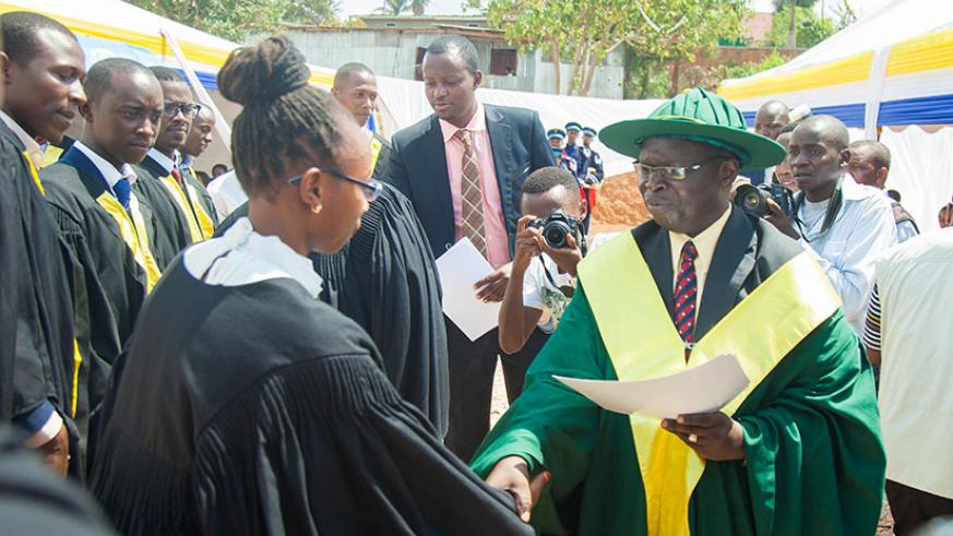 Prof Peter Opio, KIM-University vice chancellor, gives graduates their degree certificates during on Friday. (Nadege Imbabazi)