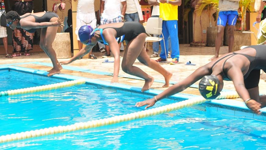 Female competitors dive into the pool during the one-day swimming competition held at Hill Top Hotel in Remera, which was dominated by Riviera High School Club. Courtesy.