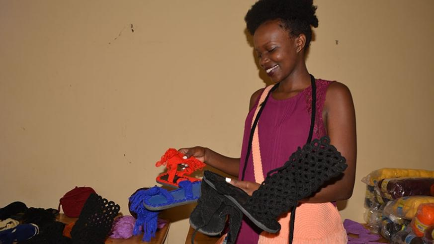 Ahirwe admires some of the products made by Posh Creative Ltd. (Photos by Frederic Byumvuhore)