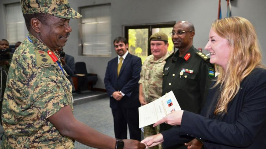 Col J K Mukasa from UPDF receives his certificate from Ms Gemma Thompson from UK High Commission to Rwanda as RPA Director Col Jill Rutaremara looks on. (Courtesy)