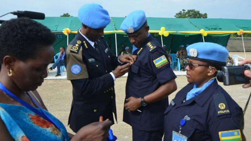 Commissioner of Police Bruce Munyambo, who represented the Special Representative of the UN Secretary-General, decorates Rwandan peacekeepers serving as Formed Police Unit under th....