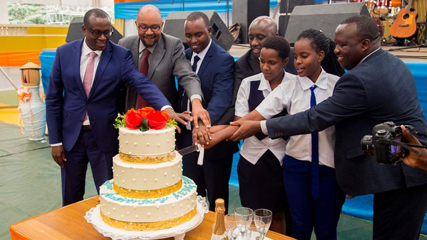 Local Government minister Francis Kaboneka joins other officials and some Association of Genocide Survivor Students (AERG) members to cut the cake as the young survivors marked the....