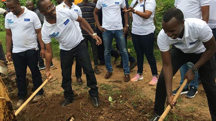 Amoateng (second left) joins Tigo staff during the event in Burera District.  (Courtesy)