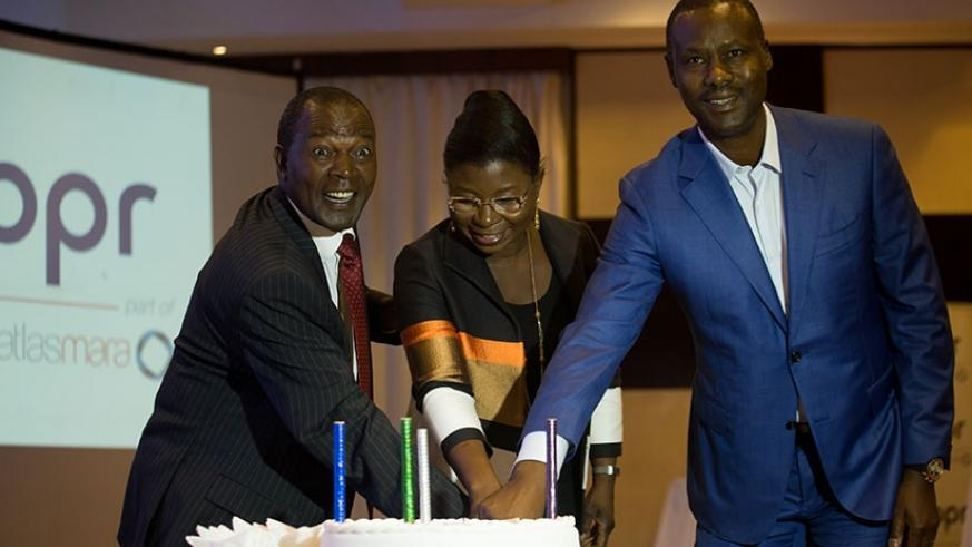 Prof Ndungu (left) cuts a cake with BPR clients at the event.  (All photos by Timothy Kisambira)