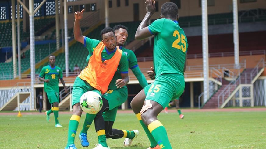 Striker Justin Mico is tackled by midfielder Ally Niyonzima as defender Yves Rugwiro closes in during Amavubi training at Amahoro Stadium on Tuesday. (Sam Ngendahimana)