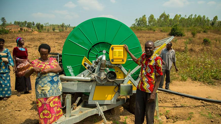 Farmers stand next to an irrigation water pump. Many SMEs don't access loans to expand their ventures. / File