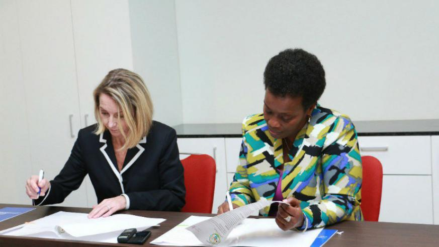 Jennifer Dent, the president of BVGH, and Dr. Gashumba sign the MoU on Thursday.