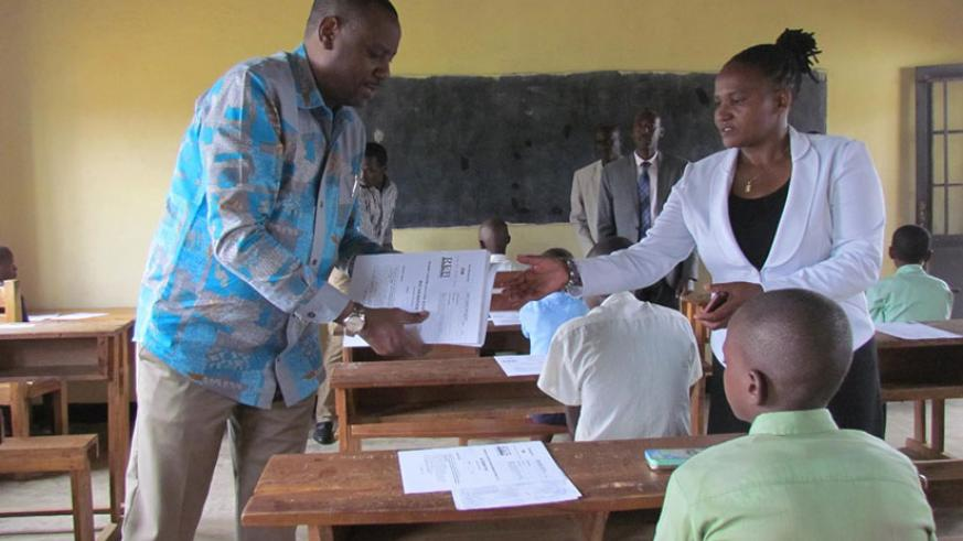 State Minister for Primary and Secondary Education, Isaac Munyakazi (L) distributes exams to candidates at GS Nyagatare on day one of PLEs (Courtesy)