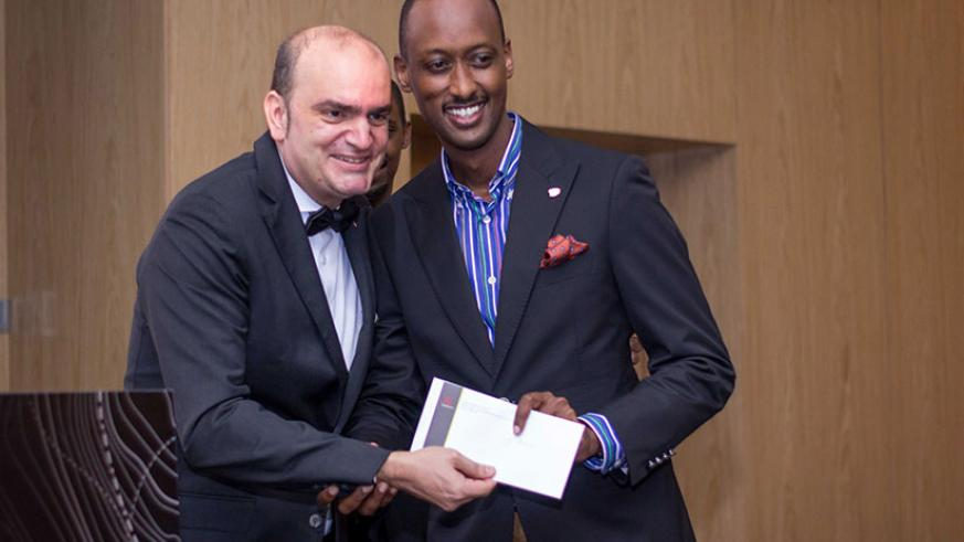 One of the clients receives his prize from Alonso (left). / Peterson Tumwebaze