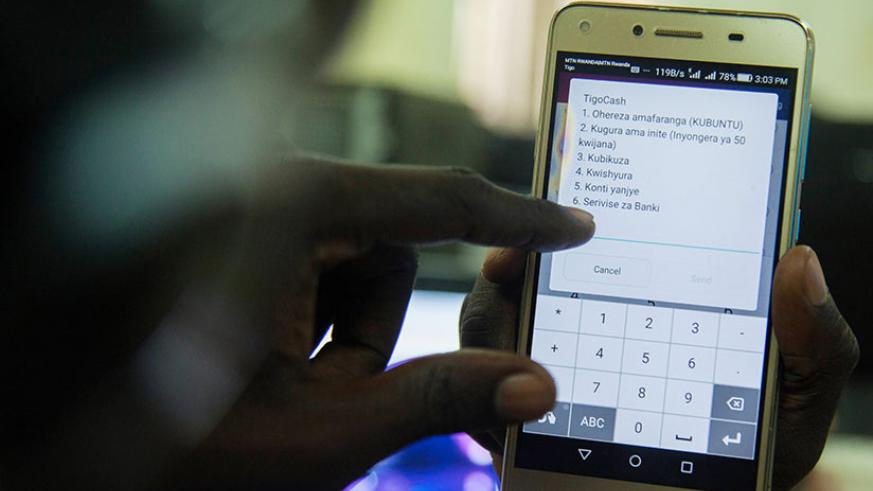 A Tigo customer makes a transaction. Iterambere Fund managers are looking to introduce mobile money payments. / File