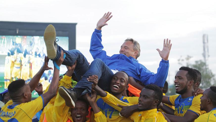 Amavubi players lift head coach Antoine Hey after drawing 0-0 with Ethiopia on Sunday at Kigali Stadium to qualify for CHAN 2018 Morocco. / Sam Ngendahimana