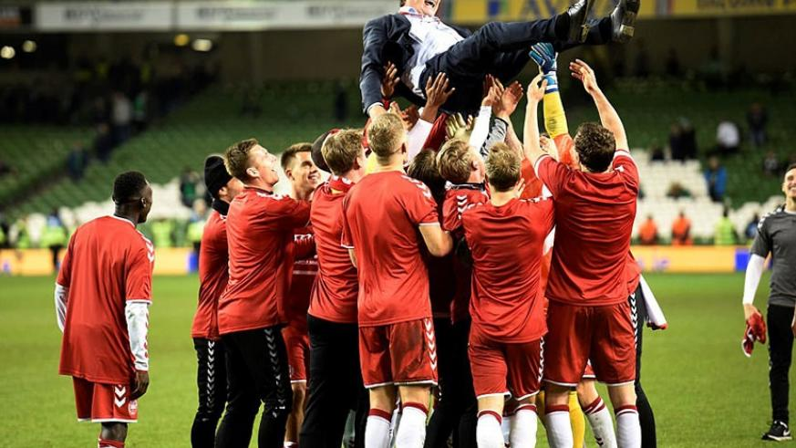 Denmark's players lift coach Age Hareide into the air after they dismantled Ireland with a clinical display on Tuesday night. (Net photo)