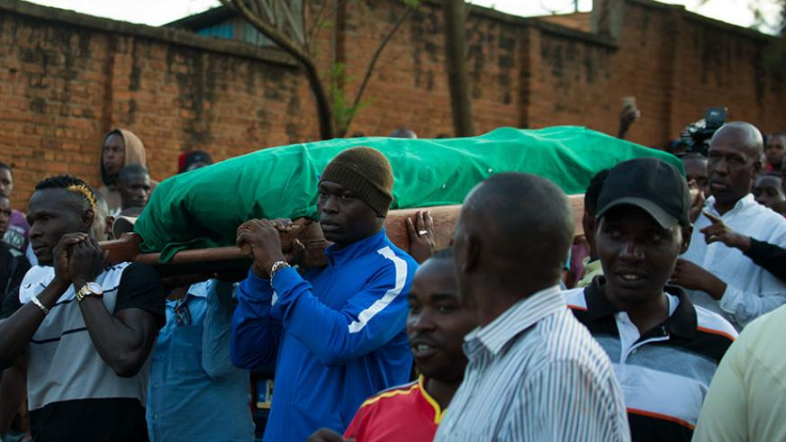 Rayon Sports players, including Ismailla Diarra (left) and Tidiane Kone (right), carry the body of the Blues' former assistant coach Hamadi Katauti Ndikumana from his home in Nyaka....