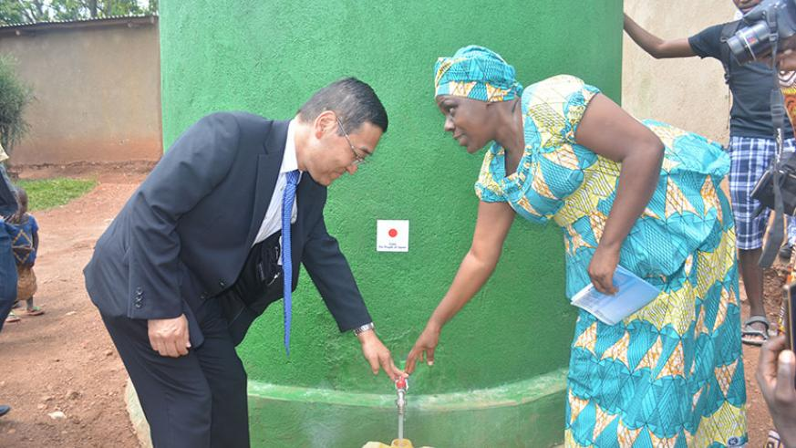 Takayuki Miyashita, the Japanese Ambassador to Rwanda together with Priscilla Uwiragiye, the Bugesera District vice-mayor in charge of social affairs fetching water from a new wate....