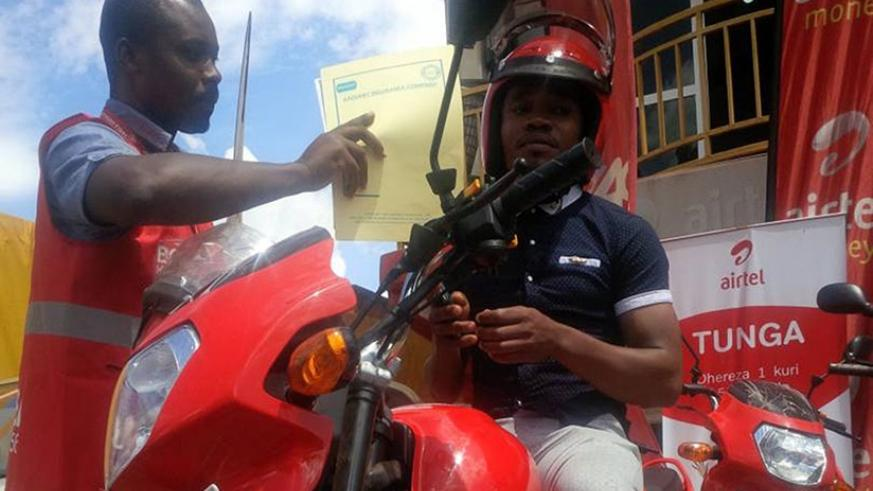 Nsabimana (right) receives the motorcycle and documents on Thursday. / Joan Mbabazi.