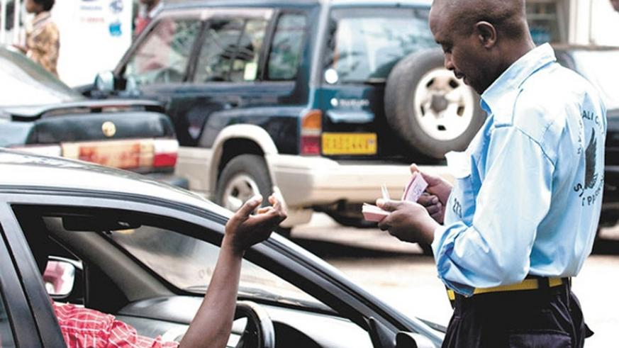 Parking official issues a ticket in Kigali. Motorists will pay for parking fees using MTN Mobile Money. File.