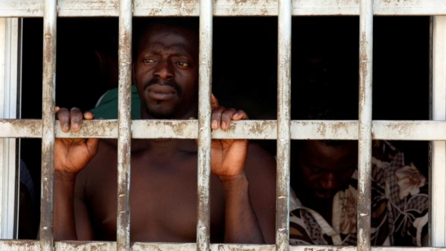 A migrant looks out of a barred door at a detention centre in Gharyan, Libya, Oct. 12, 2017. Hundreds more like him are being kept in smuggler-owned Libyan warehouses, where they a....