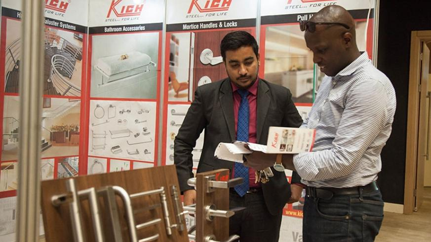 An exhibitor explains his products to visitors during BuildExpo. / Nadege Imbabazi