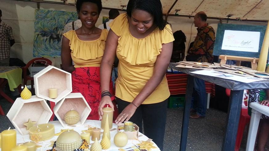 Bee Lights founder, Nathalie Neema (R), making candles from bee wax.