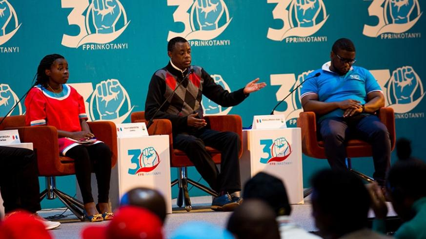 Defense minister James Kabarebe (C) speaks at the Rwanda Patriotic Front youth league congress as Clarisse Uwanyirigira (L), a youth leader, and Alain Ndagijimana, an entrepreneur ....