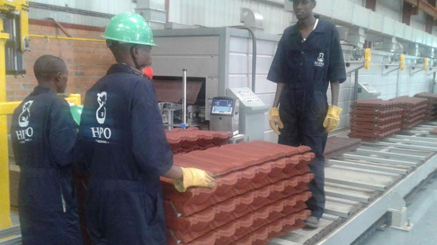 Workers of Hippo, the makers of stone coated steel roofing tiles based in Kigali Special Economic Zone. / File