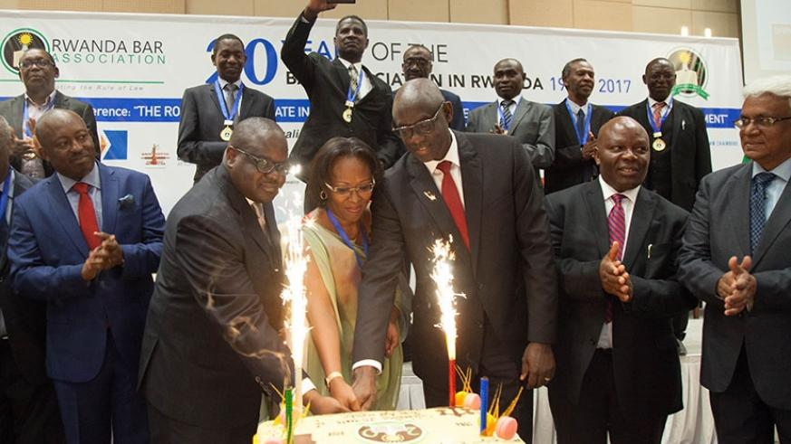 Justice minister Johnston Busingye (third right) and members of Rwanda Bar Association cut a cake during the Bar's 20th anniversary celebration in Kigali yesterday. Busingye commen....
