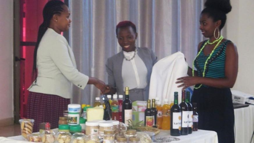 Mbabazi (left) checks out some of the products made by young agro-processors at the workshop. / Michel Nkurunziza