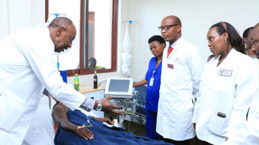 Dr. Nyirinkwaya (L) explains to the medics at Shyira how to treat an expectant mother as Dr. Gashumba looks on.